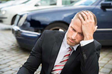 traffic accidents: Portrait Of Worried Young Man With Damaged Car