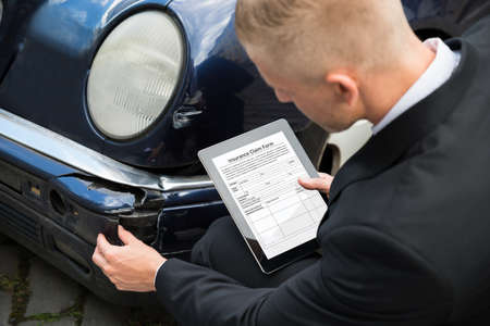 Insurance Agent Inspecting Damaged Car With Insurance Claim Form On Digital Tablet