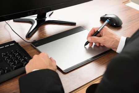 グラフィック タブレットを使用してオフィスで実業家のクローズ アップ 写真素材