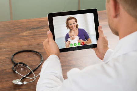 video conference: Close-up Of Doctor Talking To Patient Over Laptop Video Chat At Desk