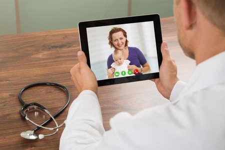 doktor: Makro lekarz mówi do pacjenta na laptopa na biurko, wideo czat