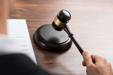 judge: Close-up Of Judge Hitting The Gavel With Contract Paper At Desk