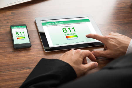 credit report: Close-up Of A Businessman Checking Credit Score Online On Digital Tablet And Cellphone