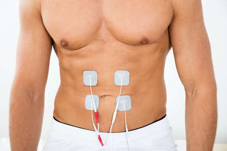 stimulator: Close-up Of Man With Electrodes On Stomach Stock Photo
