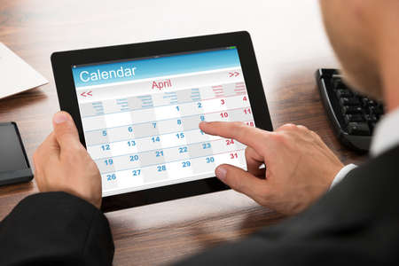 schedule: Close-up Of A Businessman Using Calendar On Digital Tablet In Office