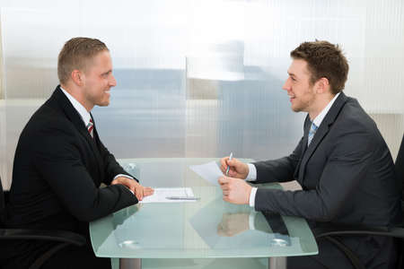 job vacancies: Happy Young Businessman Conducting An Employment Interview In The Office Stock Photo