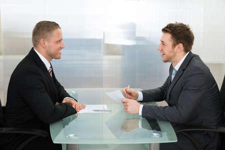 entrevista de trabajo: Hombre de negocios feliz joven que conduce una entrevista de empleo en la oficina