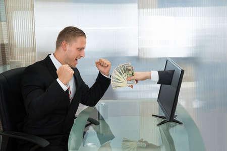 salarios: Emocionado hombre de negocios joven que mira el dinero que sale desde la pantalla plana de ordenador