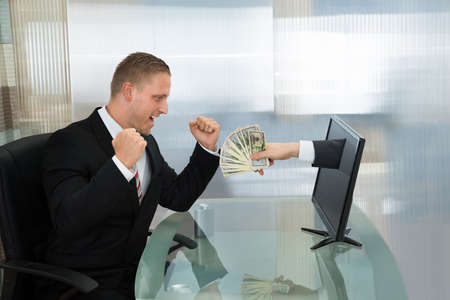 profits: Excited Young Businessman Looking At Money Coming Out From Computer Flat Screen Stock Photo