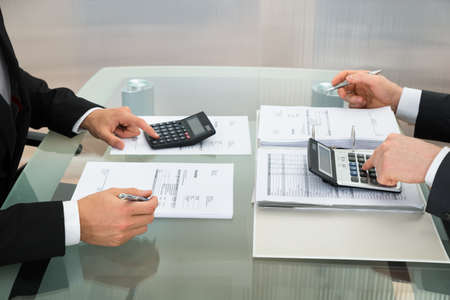 Close-up Of Two Businessman Calculating Documents Using Calculator In Office photo