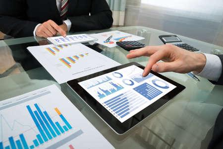 contabilidad financiera: Primer De Dos Empresario Analizar el gráfico en la tableta digital Foto de archivo