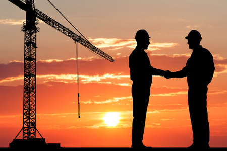 construction helmet: Silhouette Of Two Architect At Construction Site Shaking Hand Stock Photo