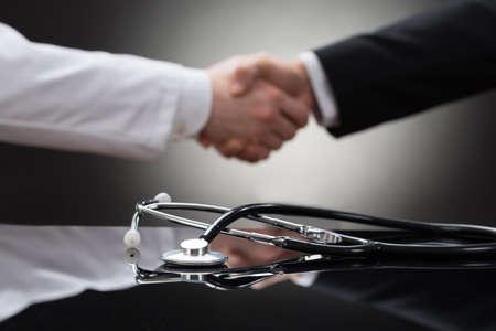 医師と聴診器の前で握手するビジネスマン