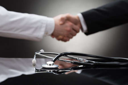 of shake: Doctor And Businessman Shaking Hand In Front Of Stethoscope Stock Photo
