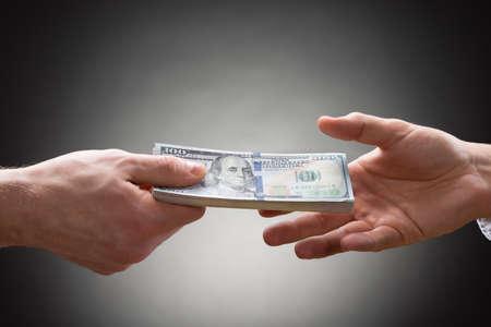もう一方の手にお金を与える人の手のクローズ アップ