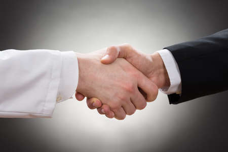 trust: Close-up Of A Doctor And Businessman Shaking Hand Stock Photo
