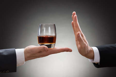 Close-up Of Businessman Hand Reject A Glass Of Whisky Offered By Businessperson Archivio Fotografico