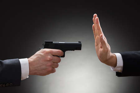 stringent: Close-up Of Businessman Hand With Gun Pointing Towards Businessperson Gesturing Stop Sign
