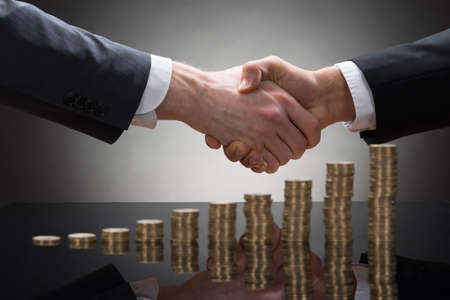 financial leadership: Close-up Of Two Businessmen Shaking Hands With Stack Of Coins Stock Photo