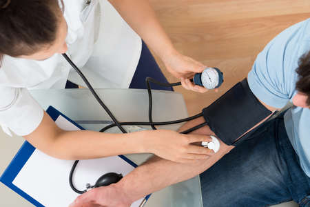 Close-up Of Female Doctor Checking Blood Pressure Of Male Patient Banque d'images