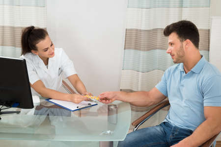 doctor holding pills: Young Female Doctor Giving Pills To Male Patient In Clinic Stock Photo