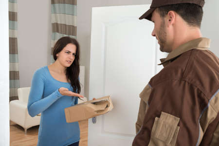 Woman Shouting On Delivery Man For Damaged Package At Doorway Foto de archivo