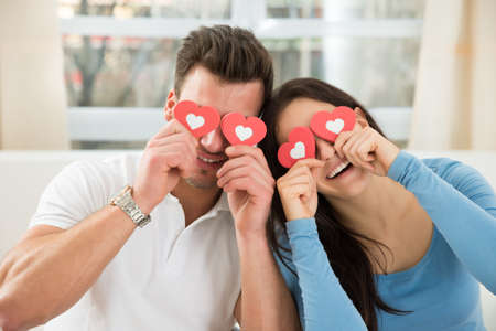 covering eyes: Young Happy Couple Covering Eyes With The Red Hearts