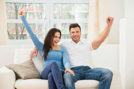 contented: Portrait Of Ecstatic Couple Sitting On Couch At Home Stock Photo