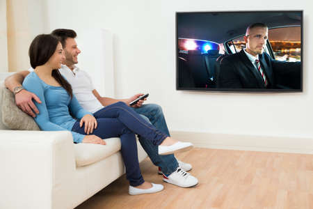 woman watching tv: Happy Young Couple In Livingroom Sitting On Couch Watching Movie