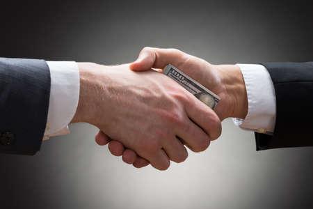 お金で手を振って 2 つのビジネスマンのクローズ アップ