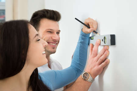 Happy Couple Marking With Pencil On Wall With Level In House photo