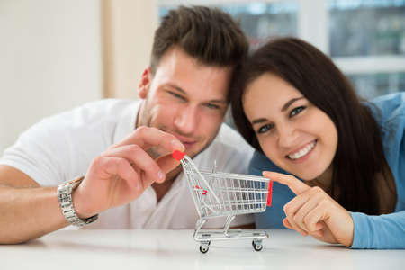 young couple smiling: Close-up Of Smiling Young Couple With Miniature Empty Shopping Cart