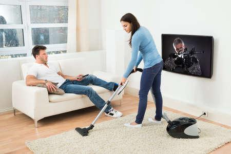 텔레비전을 보는 남자의 앞에 카펫 청소 여자