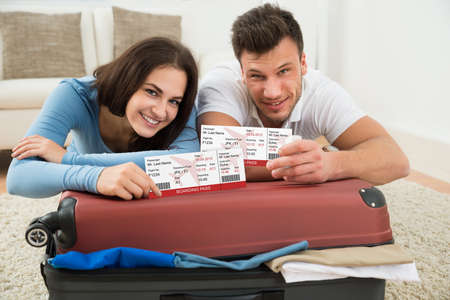 pass on: Portrait Of Happy Young Couple Packing Luggage Showing Boarding Pass Stock Photo