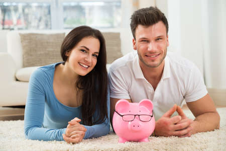 money management: Portrait Of Happy Young Couple With Piggybank Lying On Carpet Stock Photo