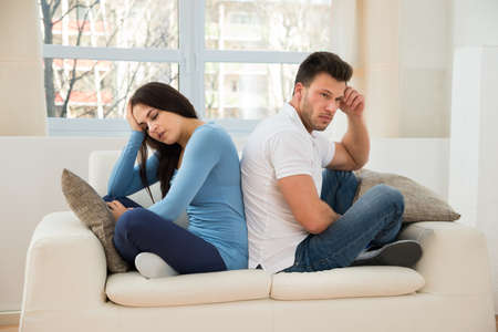 upset man: Portrait Of A Displeased Couple Sitting Back To Back On Couch