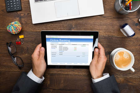online service: Close-up Of Businessman Using Online Banking Service On Digital Tablet Stock Photo