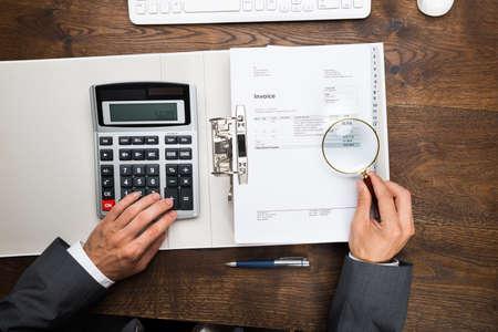Businessman Examining Invoice Through Magnifying Glass At Desk photo