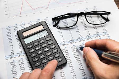 Close-up Of Businessman's Hand Calculating Financial Sheet Using Calculator Banco de Imagens