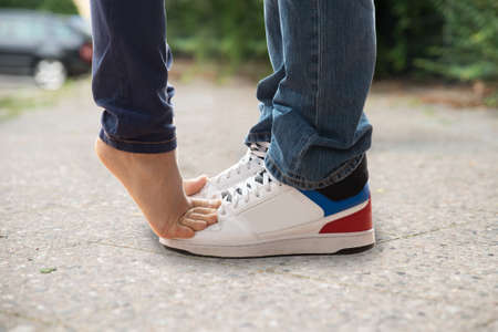 Close-up Of Kissing Couple Feet's On Street