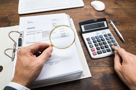 Close-up Of Businessperson Hand Examining Bills With Magnifying Glass At Desk photo