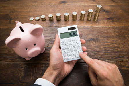 piggies: Businessman Using Calculator With Piggybank And Stack Of Coins On Desk