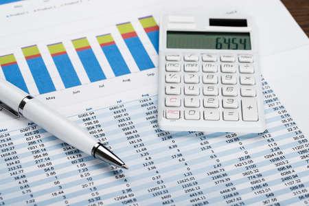 registros contables: Primer plano de una hoja de datos financieros con la calculadora y bolígrafo