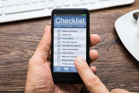 tasks: Close-up Of Person Hands Filling Checklist On Mobile Phone At Wooden Desk