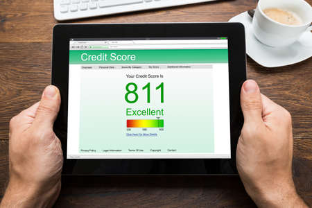 credit report: Close-up Of Person Hands With Digital Tablet Showing Credit Score At Desk