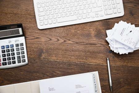 机の上のキーボードと領収書と電卓のハイアングル