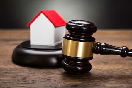 pledge: Close-up Of House Model With Gavel On Wooden Table Stock Photo