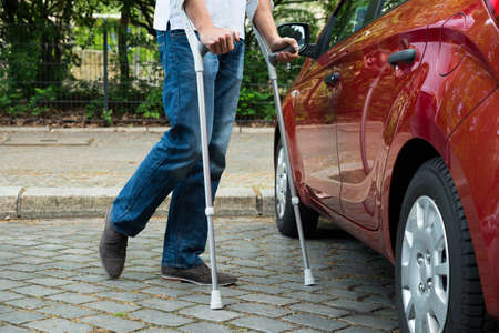 Close-up Of A Disabled Man With Crutches Walking Near Care