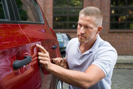 Close-up van een jonge man op zoek naar krassen op Zijn Red Car Stockfoto