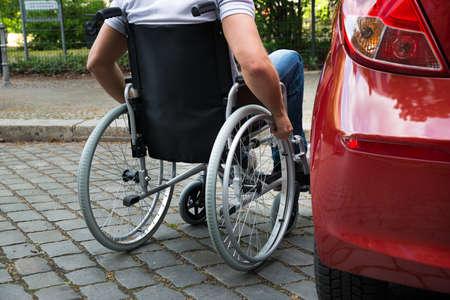 persona en silla de ruedas: Primer plano de un hombre sentado en una silla de ruedas cerca de su coche